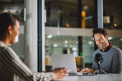 Buy stock photo Cropped shot of a handsome mature businessman being interviewed by a female colleague during a late night broadcast
