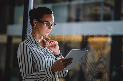 Buy stock photo Cropped shot of an attractive young businesswoman looking contemplative while standing alone in her office and using her tablet