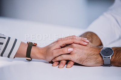 Buy stock photo Cropped shot of two unrecognizable business colleagues holding hands supportively in the office