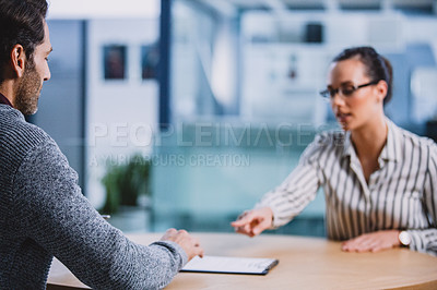 Buy stock photo Cropped shot of an attractive young businesswoman sitting with a male colleague and pointing out where to sign the contract