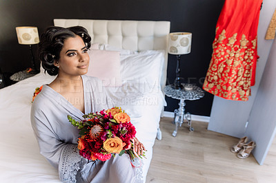 Buy stock photo Shot of a beautiful young woman holding a bunch of flowers and looking thoughtful before her wedding
