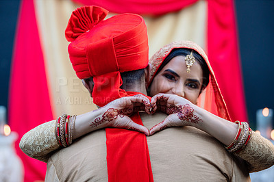 Buy stock photo Shot of a happy young woman hugging her husband and making a heart gesture on their wedding day