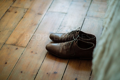 Buy stock photo Shot of two formal men's shoes on the floor of a bedroom