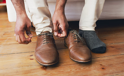 Buy stock photo Cropped shot of an unrecognizable man putting on shoes in preparation for his wedding