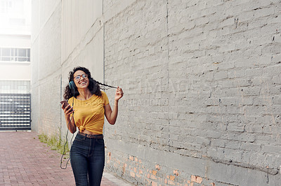 Buy stock photo Cropped shot of an attractive young woman wearing headphones and listening to music through her cellphone while outdoors