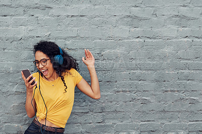 Buy stock photo Cropped shot of an attractive young woman wearing headphones and dancing while listening to music through her cellphone