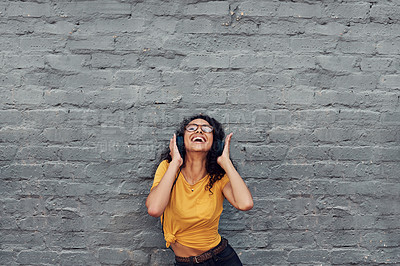 Buy stock photo Cropped shot of an attractive young woman wearing headphones and dancing while listening to music outdoors
