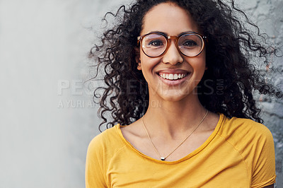 Buy stock photo Cropped portrait of an attractive young woman wearing spectacles and smiling while standing against a gray background outdoors