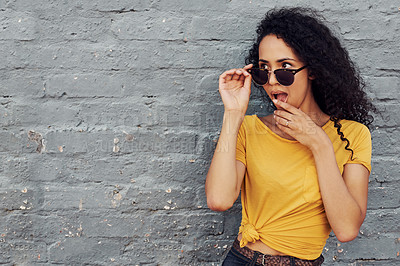 Buy stock photo Cropped shot of an attractive young woman wearing sunglasses and looking flirtatious while standing alone against a gray background