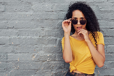 Buy stock photo Cropped portrait of an attractive young woman wearing sunglasses and looking flirtatious while standing alone against a gray background