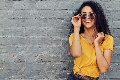 Buy stock photo Cropped portrait of an attractive young woman wearing sunglasses and smiling while standing against a gray background outdoors