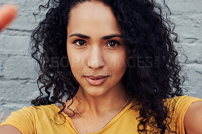 Buy stock photo Cropped portrait of an attractive young woman standing alone and posing for a selfie against a gray background