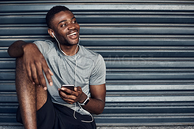Buy stock photo Shot of a sporty young man wearing earphones while using a cellphone against a grey background