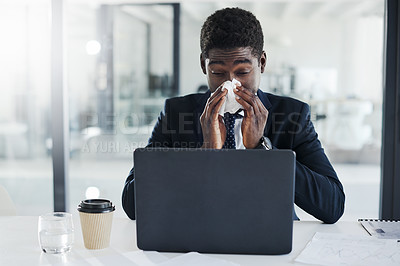 Buy stock photo Shot of a young businessman blowing his nose while working on a laptop in an office