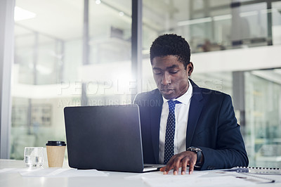 Buy stock photo Shot of a young businessman going through paperwork while working on a laptop in an office