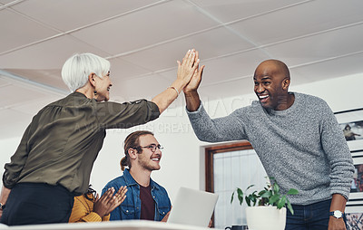 Buy stock photo Cropped shot of two cheerful businesspeople giving each other a high five inside of the office during the day
