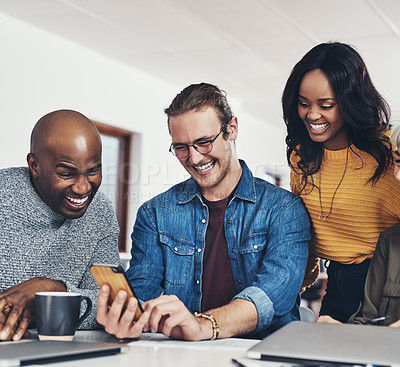 Buy stock photo Cropped shot of a group of cheerful businesspeople browsing on a cellphone together inside of the office during the day