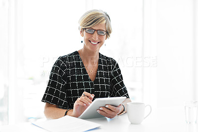 Buy stock photo Cropped portrait of an attractive mature businesswoman smiling while working with a digital tablet in her office