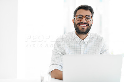 Buy stock photo Cropped portrait of a handsome young businessman smiling while working on a laptop in his office
