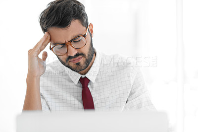 Buy stock photo Cropped shot of a handsome young businessman suffering with a headache while working in a modern office