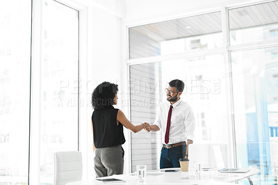 Buy stock photo Cropped shot of two young businesspeople shaking hands while standing in a modern office