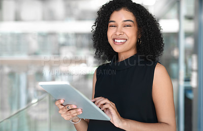 Buy stock photo Cropped portrait of an attractive young businesswoman using a digital tablet while standing in a modern office
