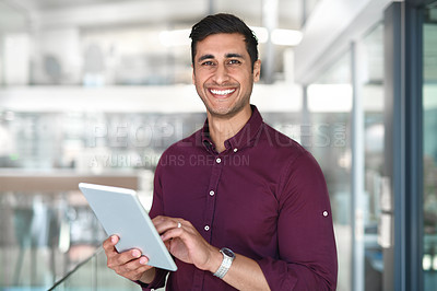 Buy stock photo Cropped portrait of a handsome young businessman using a digital tablet while standing in modern office