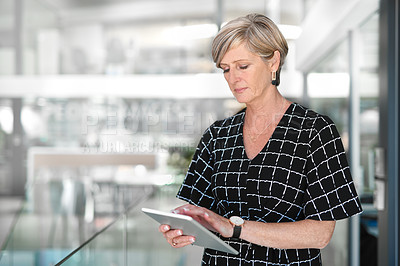 Buy stock photo Cropped shot of an attractive mature businesswoman using a digital tablet while standing in a modern office