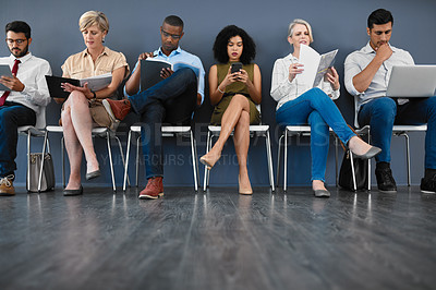 Buy stock photo Studio shot of a group of businesspeople keeping occupied while sitting in line against a grey background