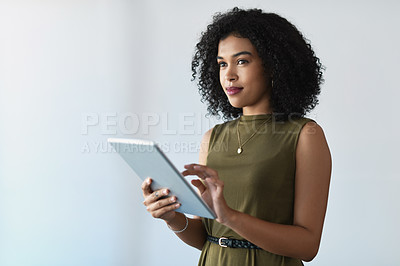 Buy stock photo Cropped shot of an attractive young businesswoman looking thoughtful while using  a digital tablet in a modern office