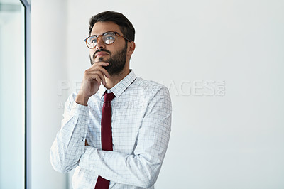 Buy stock photo Cropped shot of a handsome young businessman looking thoughtful while standing in a modern office