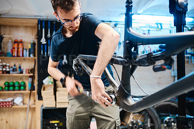 Buy stock photo Shot of a young man fixing a bicycle in a workshop