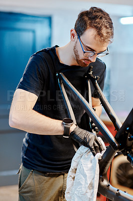 Buy stock photo Shot of a young man wiping a bicycle with a cloth in a workshop