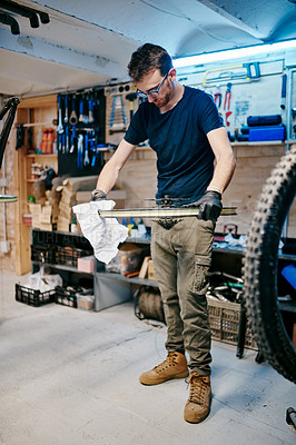 Buy stock photo Shot of a young man wiping a bicycle wheel with a cloth in a workshop