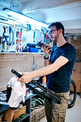 Buy stock photo Shot of a young man using a cellphone while working in a bicycle repair shop