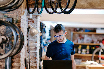 Buy stock photo Shot of a young man using a laptop in a bicycle workshop
