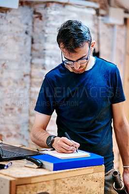 Buy stock photo Shot of a young man writing notes while working in a bicycle repair shop