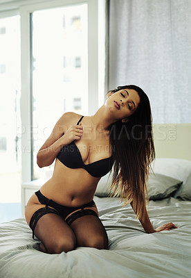 Buy stock photo Full length shot of an attractive young woman kneeling on her bed while wearing lingerie