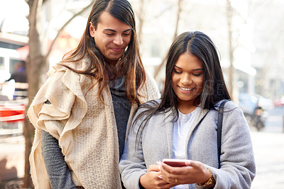 Buy stock photo Cropped shot of two affectionate young friends using a smartphone together while standing outdoors
