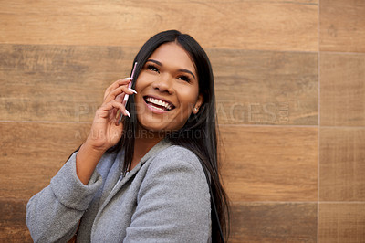 Buy stock photo Cropped shot of an attractive young woman smiling while taking a phonecall outdoors