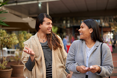 Buy stock photo Cropped shot of two affectionate young friends laughing together while walking outdoors