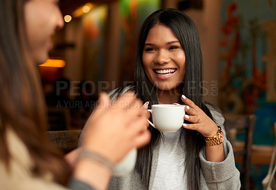 Buy stock photo Cropped shot of an affectionate young woman smiling while having coffee with her friend in a cafe