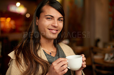 Buy stock photo Cropped portrait of a young gender fluid person smiling while holding a cup of coffee in a cafe