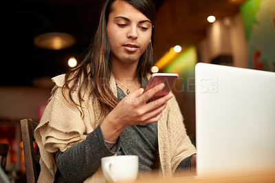 Buy stock photo Cropped shot of a young gender fluid person using a smartphone and a laptop in a coffee shop