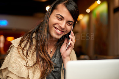 Buy stock photo Cropped shot of a young gender fluid person taking a phonecall while using a laptop in a cafe
