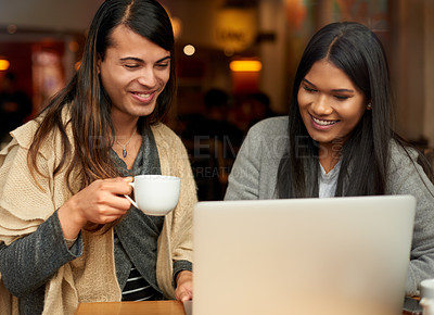 Buy stock photo Cropped shot of two affectionate young friends using a laptop together while having coffee in a cafe