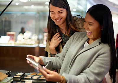 Buy stock photo Cropped shot of two affectionate young friends laughing together while looking at a makeup kit in a cosmetics shop