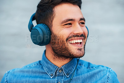 Buy stock photo Cropped shot of a handsome young man smiling while listening to music on his headphones against a brick wall