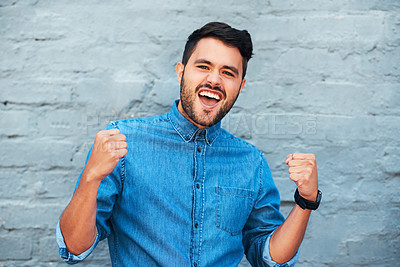 Buy stock photo Cropped portrait of a handsome young man cheering while standing against a brick wall