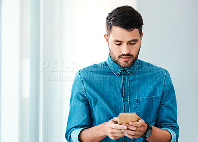 Buy stock photo Cropped shot of a handsome young businessman using a mobile phone while standing in an office